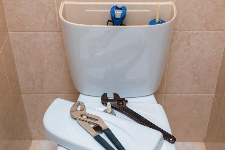 toilet repair with plumbing tools